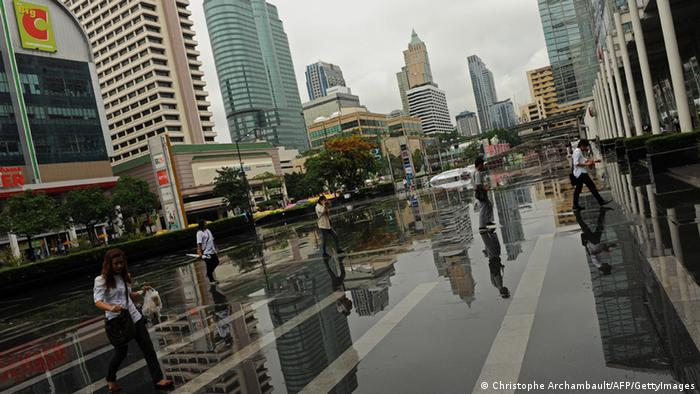 Thai people are reflected in a puddle in Bangkok (photo: CHRISTOPHE ARCHAMBAULT/AFP/GettyImages)