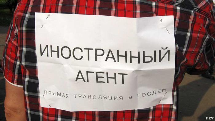 Прикрепленный к спине мужчины лист бумаги с надписью иностранный агент