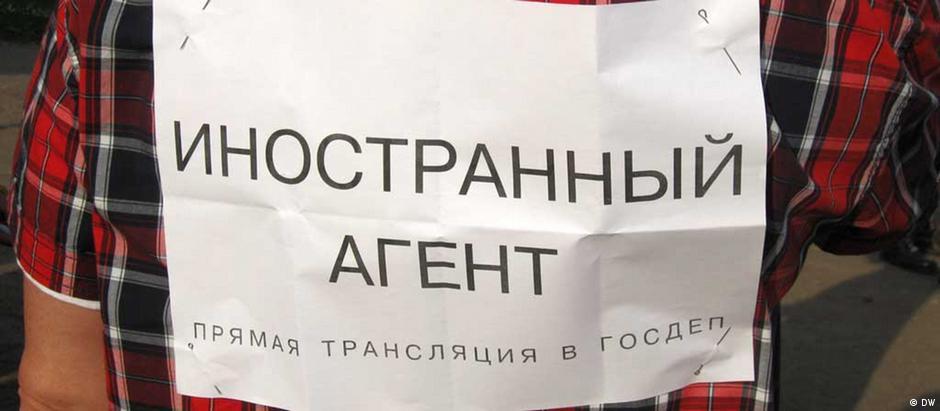 Плакат с надписью иностранный агент на спине у человека