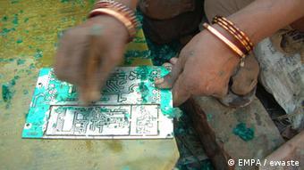 A woman scrapes plastic off of a board