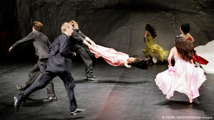 Tänzer schwingen und springen heftig über eine schwarze Bühne.  AFP PHOTO/PIERRE VERDY (Photo credit should read PIERRE VERDY/AFP/Getty Images)