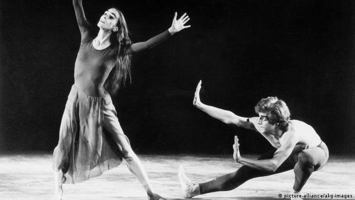 Eine schwarzweiße Fotografie von Pina Bausch, tanzend auf der Bühne und dem Tänzer Iwan Neumann hinter ihr. (c) picture-alliance/akg-images