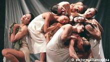 Dançarinos de branco realizam movimentos e contorcionismo