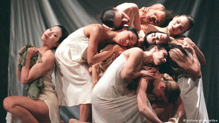 Mehrer Tänzer in weißen Hemden und Kleidern winden sich ineinander. (c) dpa