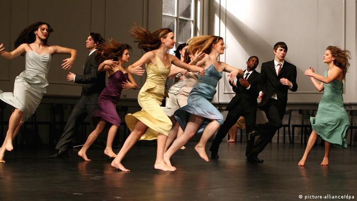 Tänzerinnen in bunten Kleidern rennen über die Bühne. Foto: Bernd Thissen dpa/lnw