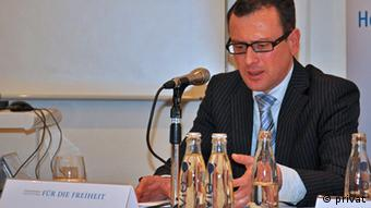 Rolf-Ulrich Kunze sits on a podium behind a microphone. (Photo: private (all rights granted))