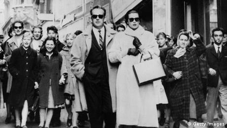 Prince Rainier of Monaco (C-L) and Princess Grace come down a Lausanne street followed by residents. The couple just arrived there for a few days of vacations shortly after the birth of Princess Caroline (Photo credit should read DSK/AFP/Getty Images).