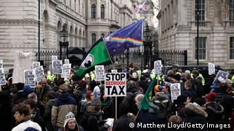 LONDON, ENGLAND - MARCH 30: Protestors hold signs as they demonstrate against the proposed bedroom tax gather in Trafalgar Square