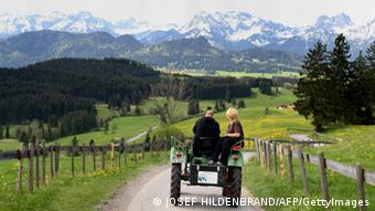 Tourists enjoy their ride on a hired tractor near Pfronten, southern Germany, on May 2, 2012. Tractors can be chartered by the hour to explore cross-country roads on this old vehicle. AFP PHOTO / KARL-JOSEF HILDENBRAND GERMANY OUT (Photo credit should read KARL-JOSEF HILDENBRAND/AFP/GettyImages)