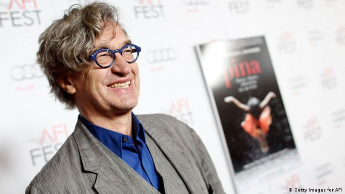 Der Regisseur Wim Wenders steht vor einem Plakat seines Films Pina 