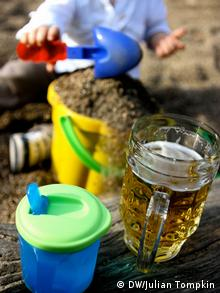 Children's cup and beer glass in the foreground, child playing in the sand in the background