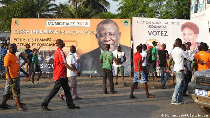A picture taken on April 11, 2013 in the Koumassi district of Abidjan shows people walking past posters of candidates for the April 21 local elections. The party of Ivorian President Alassane Ouattara on April 17, 2013 voiced concern over growing political tension ahead of local polls meant to cement post-conflict stabilisation. AFP PHOTO/ SIA KAMBOU (Photo credit should read SIA KAMBOU/AFP/Getty Images)