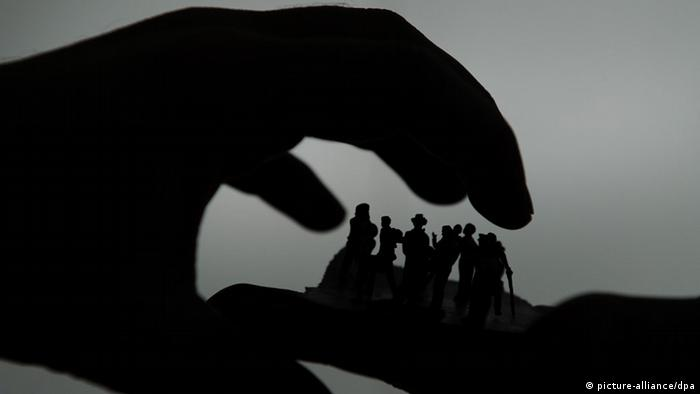 A silhouette of a hand grabbing hold of people