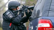 A member of the SWAT team trains a gun on an apartment building during a search for the remaining suspect in the Boston Marathon bombings in Watertown, Massachusetts April 19, 2013. Two Boston bomb suspects were named as brothers, Dzhokhar A. Tsarnaev, 19, and his brother Tamerlan Tsarnaev, 26, a U.S. national security official said on Friday. The official said the older brother died in a shootout with police and the younger one was being sought in a house-to-house search for in the Boston suburb of Watertown. REUTERS/Jessica Rinaldi (UNITED STATES - Tags: CIVIL UNREST CRIME LAW)