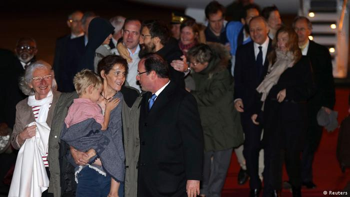 Former hostage Albane Moulin-Fournier (front 2nd L) speaks with French President Francois Hollande (front R) as she holds one of her children, while Cyril Moulin-Fournier (back R, in black) is hugged by Romain Striffing, brother of Albane Moulin-Fournier, at their arrival at Orly Airport, April 20, 2013. (Photo: REUTERS/Philippe Wojazer)
