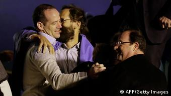 French President Francois Hollande (R) welcomes members of the Moulin-Fournier family as they arrive from Yaounde, at the Orly airport, near Paris, on April 20, 2013. (Photo: KENZO TRIBOUILLARD/AFP/Getty Images)