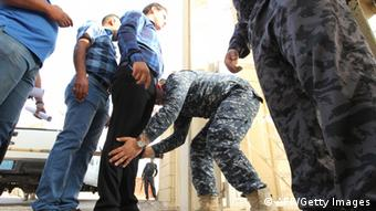 Iraqi security forces frisk men arriving to cast their votes at a polling station during provincial elections on April 20, 2013 in Baghdad. (Photo: SABAH ARAR/AFP/Getty Images)