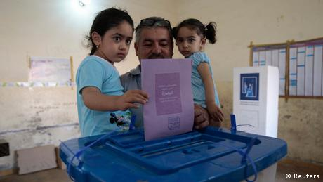 A man holds his daughters as he casts his ballot during Iraq's provincial elections, April 2013. (Photo: Atef Hassan)