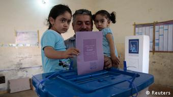 A man holds his daughters as he casts his ballot during the country's provincial elections at a polling station in Basra, 420 km (261 miles) southeast of Baghdad, April 20, 2013. (Photo: REUTERS/Atef Hassan)
