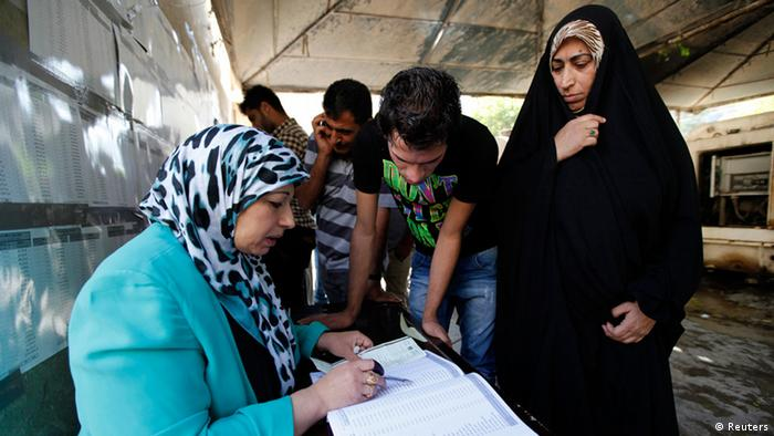 Residents register their names before voting at a polling station in Baghdad April 20, 2013. Iraqis voted for provincial councils on Saturday in their first ballot since U.S. troops left the country, a key measure of political strength before parliamentary elections next year. Iraqi politics are deeply split along sectarian lines with Prime Minister Nuri al-Maliki's government mired in crisis over how to share power among Shi'ites, Sunni Muslims and ethnic Kurds who run their own autonomous region in the north. Violence and suicide bombings have surged since the start of the year with a local al-Qaeda wing vowing a campaign to stoke widespread confrontation among the country's combustible sectarian and ethnic mix. REUTERS/Mohammed Ameen (IRAQ - Tags: POLITICS ELECTIONS)