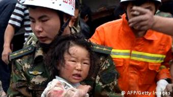 GettyImages 167095103 A rescuer carries a child to safety after she was pulled out of her collapsed home after an earthquake hit Ya'an City in Lushan county, southwest China's Sichuan province on April 20, 2013. More than 100 people were killed and 3,000 injured when a strong earthquake shook southwest China on April 20, wrecking homes and triggering landslides in an area devastated by a major tremor in 2008. CHINA OUT AFP PHOTO (Photo credit should read STR/AFP/Getty Images)