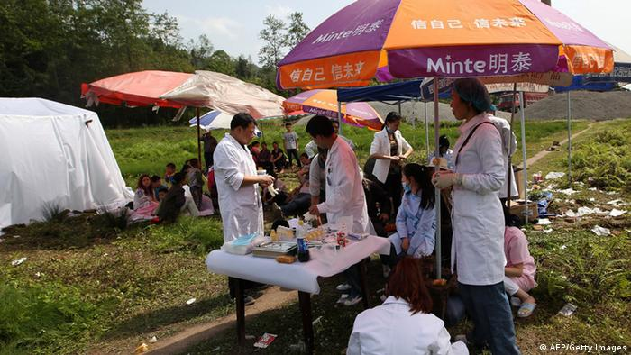 GettyImages 167095056 Medical personnel offer help to local residents in Longmen township, an area very close to the epicenter of a shallow earthquake at magnitude 7.0 that hit the city of Ya'an, southwest China's Sichuan province on April 20, 2013. More than 100 people were killed and 3,000 injured when a strong earthquake shook southwest China on April 20, wrecking homes and triggering landslides in an area devastated by a major tremor in 2008. CHINA OUT AFP PHOTO (Photo credit should read STR/AFP/Getty Images)