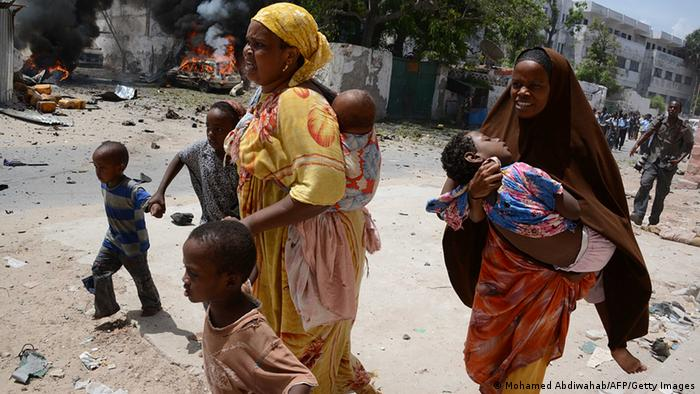 Two mothers run with their children on April 14, 2013, in Mogadishu, after a suicide bomber attack AFP PHOTO / MOHAMED ABDIWAHAB