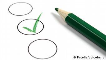 Symbolbild grüner Stift Wahlzettel Stimmzettel Stimme Haken Häkchen Auswahl