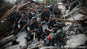 Rescuers sit on ruins of a house in Longmen township, an area very close to the epicenter of a shallow earthquake at magnitude 7.0 that hit the city of Ya'an, southwest China's Sichuan province on April 20, 2013. The death toll from this earthquake on April 20 in China's southwestern Sichuan province has reached 100 with more than 2,000 others injured, government officials said. CHINA OUT AFP PHOTO (Photo credit should read STR/AFP/Getty Images)