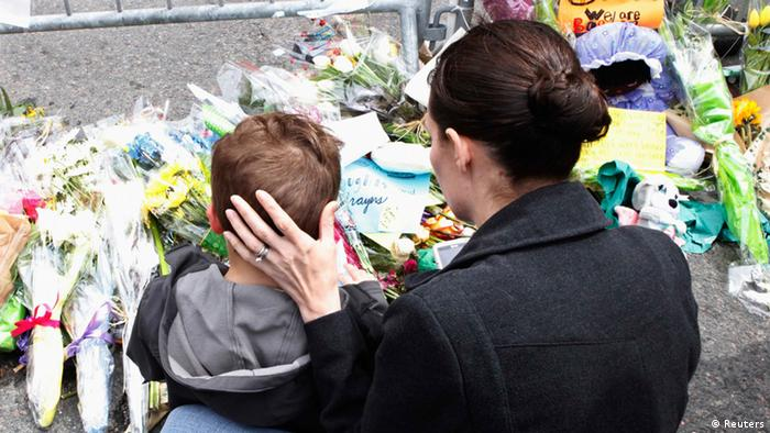 A woman comforts her son as they sit at a memorial for victims near the scene of the Boston Marathon bombings in Boston, Massachusetts, April 20, 2013. With Dzhokhar Tsarnaev, the surviving suspect in the Boston Marathon bombings lying seriously wounded in a hospital, investigators worked on Saturday to find a motive and whether the ethnic Chechen brothers accused in the attack acted alone. REUTERS/Jim Bourg (UNITED STATES - Tags: CRIME LAW CIVIL UNREST)