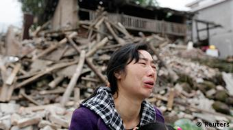 Song Zhengqiong, a survivor, cries in front of her damaged house (Photo: REUTERS/Jason Lee)