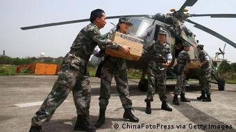 Rescue workers load relief supplies onto a helicopter (Photo by ChinaFotoPress/ChinaFotoPress via Getty Images)