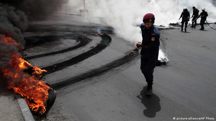 Riot police extinguish a row of burning tires set ablaze by Bahraini anti-government protesters, not pictured, on a street in Jidhafs, Bahrain, Sunday, April 21, 2013. (AP Photo/Hasan Jamali)