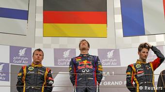 Winner Red Bull Formula One driver Sebastian Vettel of Germany (C) stands beside second placed Lotus Formula One driver Kimi Raikkonen of Finland (L) and third placed Lotus Formula One driver Romain Grosjean of France during the victory ceremony of the Bahrain F1 Grand Prix at the Sakhir circuit, south of Manama April 21, 2013. (Photo: REUTERS/Caren Firouz)
