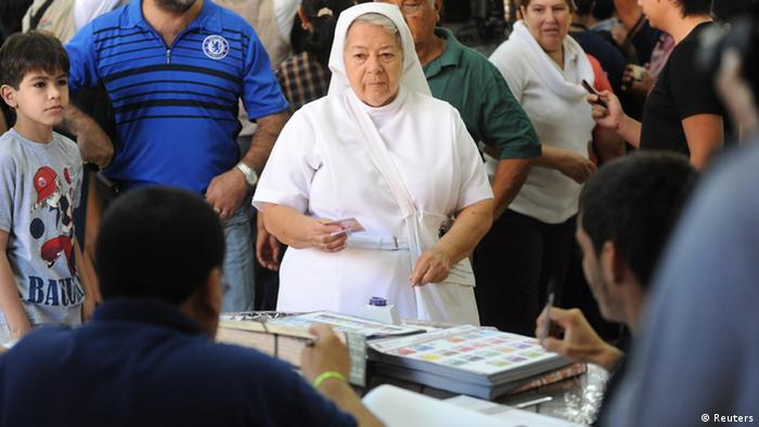 A nun prepares to cast her vote at a polling station in Asuncion on Sunday. Voters in Paraguay are casting ballots to choose a new leader and turn the page on a political crisis that saw the impeachment of leftist president Fernando Lugo ten months ago. (Photo: Norberto Duarte/AFP/Getty Images)
