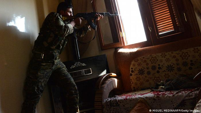 A Kurdish fighter from the Popular Protection Units (YPG) fires towards Syrian government forces inside a building in the majority-Kurdish Sheikh Maqsud district of the northern Syrian city of Aleppo, on April 21, 2013. Syria's National Coalition head Ahmad Moaz al-Khatib has refiled his resignation and an interim leader is being sought, a fellow member and a source close to the main opposition group said. AFP PHOTO/MIGUEL MEDINA (Photo credit should read MIGUEL MEDINA/AFP/Getty Images)