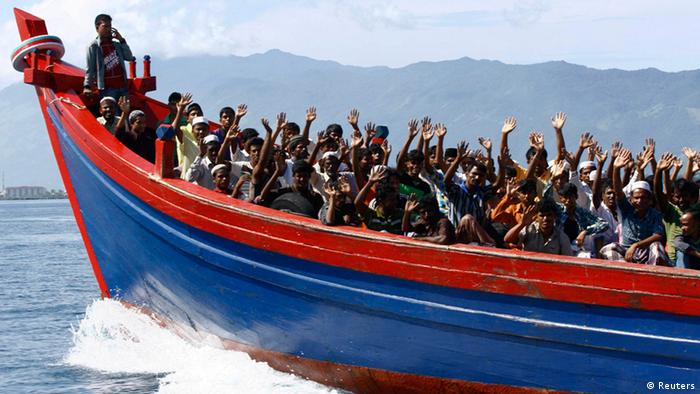 Ethnic Rohingya refugees from Myanmar wave as they are transported by a wooden boat to a temporary shelter in Krueng Raya in Aceh Besar April 8, 2013. (Photo: REUTERS/Junaidi Hanafiah)