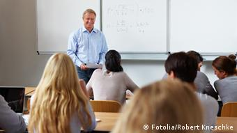 Teacher at whiteboard in front of classroom