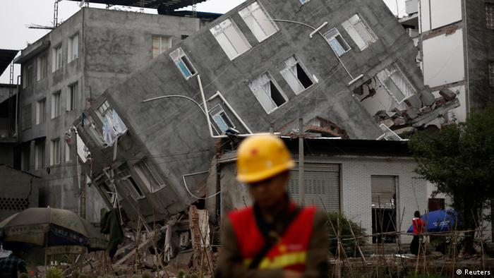 A rescuer walks in front of a damaged building after Saturday's earthquake in Lingguan town of Baoxing county, Sichuan province April 22, 2013. Rescuers struggled to reach a remote, rural corner of southwestern China on Sunday as the toll of the dead and missing from the country's worst earthquake in three years climbed to 208 with almost 1,000 serious injuries. The 6.6 magnitude quake struck in Lushan county, near the city of Ya'an in the southwestern province of Sichuan, close to where a devastating 7.9 quake hit in May 2008, killing 70,000. REUTERS/Aly Song (CHINA - Tags: DISASTER ENVIRONMENT TPX IMAGES OF THE DAY)