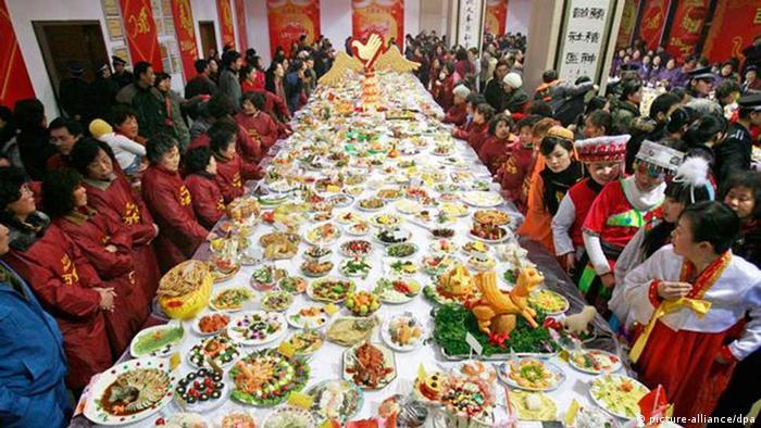 Eine Festtafel in einem asiatischen Land mit unzähligen Speisen und festlich gekleidete Menschen