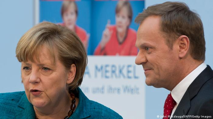 Polish Prime Minister Donald Tusk (R) and German Chancellor Angela Merkel chat before leaving the venue where they held a discussion on 'Europe' in Berlin on April 22, 2013. The discussion coincides with the release of a biography of Merkel by German author and journalist Stefan Kornelius. AFP PHOTO / JOHN MACDOUGALL (Photo credit should read JOHN MACDOUGALL/AFP/Getty Images)