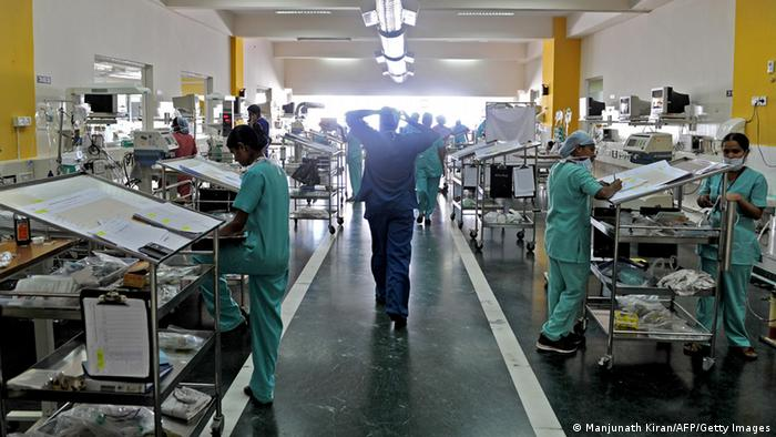 TO GO WITH India-health-hospital,FEATURE by Adam Plowright In this picture taken on February 7, 2013 hospital staff work at one of the post-operative pediatrics observation and care units of the Narayana Hrudayalaya cardiac-care hospital in Bangalore. What if hospitals were run like a mix of Wal-Mart and a low-cost airline? The result might be something like the chain of no-frills Narayana Hrudayalaya clinics in southern India. Using pre-fabricated buildings, stripping out air-conditioning and even training visitors to help with post-operative care, the group believes it can cut the cost of heart surgery to an astonishing 800 USD. AFP PHOTO/Manjunath KIRAN (Photo credit should read Manjunath Kiran/AFP/Getty Images)