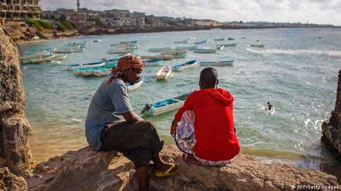 Two Somali men look across Mogadishu's fishing harbor