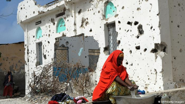 A Somali woman who was displaced from her home village due to one of the harshest droughts affecting the region in the past 60 years, washes clothes near the bullet riddled wall of a mosque in a neighborhood of Somalia's capital Mogadishu on August 15, 2011. This neighborhood saw fierce fighting between armed extremist insurgents belonging to Al-Shebab and pro-government soldiers and fighters vying for power in the city. The Al-Shebab who until recently controlled part of this neighborhood left the city a few weeks ago. Many of the Somali's who were displaced by the famine affecting the region moved into the neighborhood and are now living in makeshift shelters among the ruins. Over 100,000 people have fled into Somalia's famine-hit and war-torn capital in the past two months in search of food, water and medicine. Some 12 million people in parts of Ethiopia, Djibouti, Kenya, Uganda and Somalia are in danger of starvation in the wake of the region's worst drought in decades. War-wracked Somalia is the country hardest hit by the Horn of Africa's drought, with five areas declared to be experiencing famine. AFP PHOTO/ROBERTO SCHMIDT (Photo credit should read ROBERTO SCHMIDT/AFP/Getty Images)