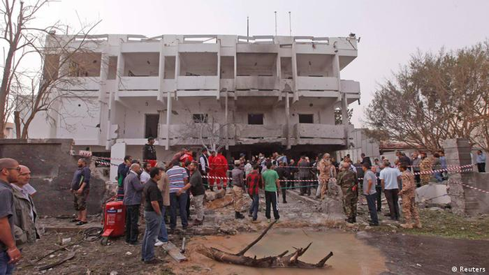 People stand among debris outside the French embassy after the building was attacked, in Tripoli (photo via Reuters)