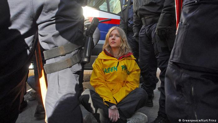 Protester sits surrounded by police at Greenpeace protest in Vienna