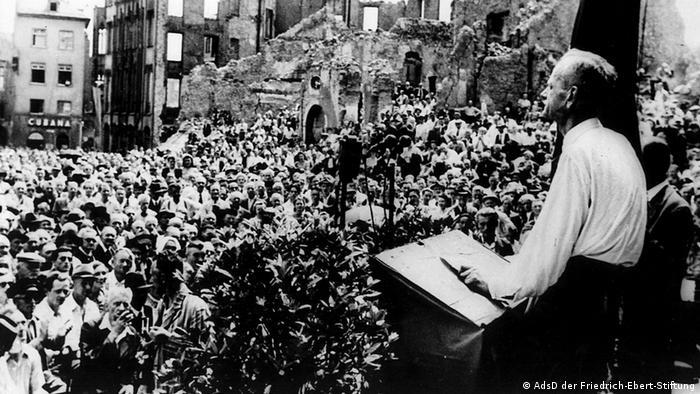 Der SPD-Vorsitzende der westlichen Besatzungszonen Kurt Schumacher spricht auf einer Kundgebung auf dem Frankfurter Römer am 27.6.1946 vor der Kulisse ausgebombter Häuserfassaden, Foto: © AdsD der Friedrich-Ebert-Stiftung