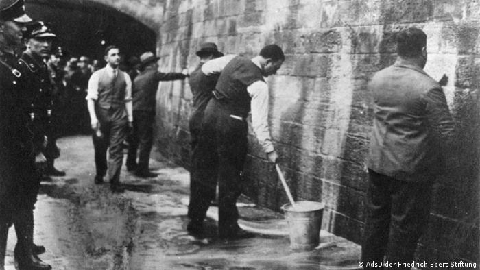 SPD-Politiker werden 1933 unter Aufsicht der SA gezwungen, Wandparolen zu entfernen, Foto: © AdsD der Friedrich-Ebert-Stiftung.