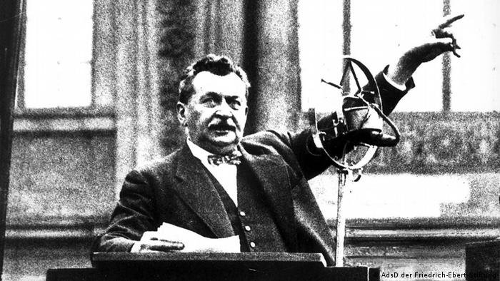 In a black-and-white photograph, a man giving a speech at a podium points his finger accusatorily (Photo: © AdsD der Friedrich-Ebert-Stiftung.)