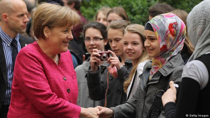 Merkel shakes hand of head-scarf-wearing woman